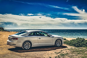 silver car sitting on hilltop overlooking beach
