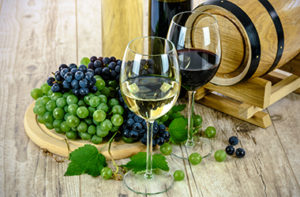 one glass of red wine and one glass of white wine in front of a small cask and grapes