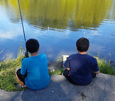 two boys with their backs to the camera holding fishing poles and fishing in a lake