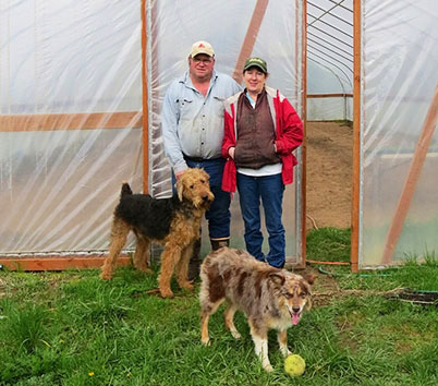 farmer Pat and his wife and dogs standing in front of a greenhouse