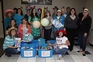 employees holding toys and other donations for MDA