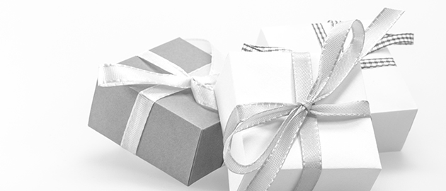 white background with white and gray wrapped gifts, tied with silver bows