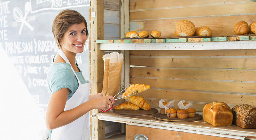 young female business owner smiling inside bakery