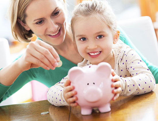 blonde haired young girl with her mother holding a piggy bank and smiling