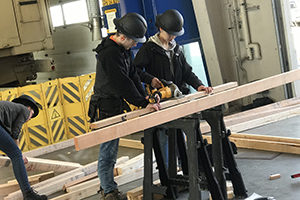 group of high school students in black hard hats cutting lumber with a power tool