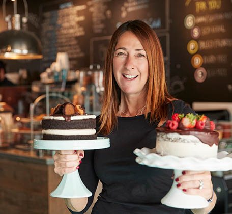 women in cafe holding cakes on stands