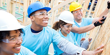 Diverse friends are volunteers working together to build home for charity. They are confidently putting up a wall in the home. They are all holding the wall. They are wearing hard hats, safety glasses and light blue volunteer t-shirts.