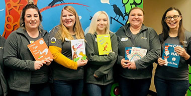 group of female InRoads employees in matching grey shirts holding Dr. Seuss books