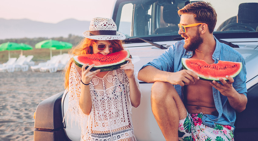 woman and man eating watermelon on the beach and sitting on a jeep