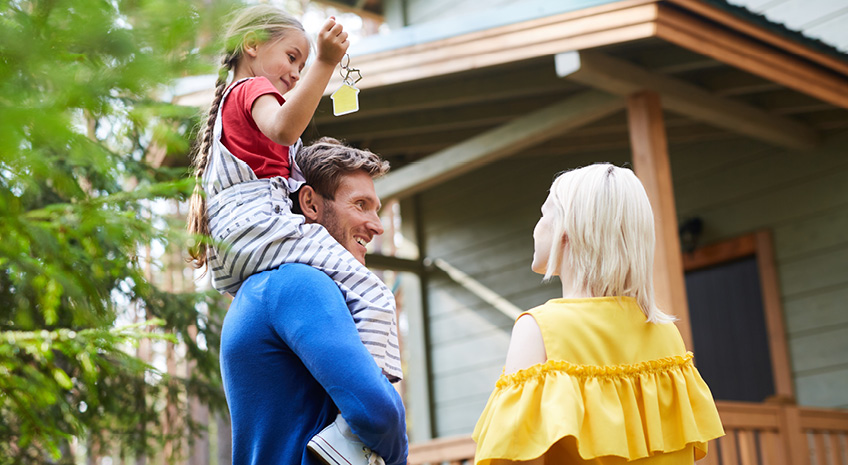 man, woman, and child standing outside home with house keys